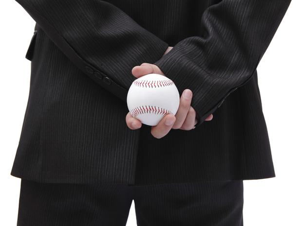 Business man holding ball in his back